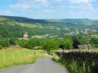 country lane running downhill surrounded by fields with sheep with a view of the town of mytholmroyd surrounded by woods and fields in the calder valley west yorkshire