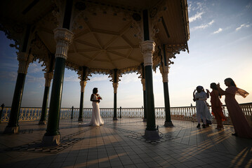 A bride poses for photographs during hot weather at Brighton beach