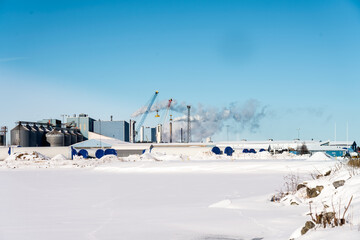 Winter view at some industrial place with many smoky or steamy pipes. Very cold sunny day, snow covers field. Big constructions are stored for windmills construction site.