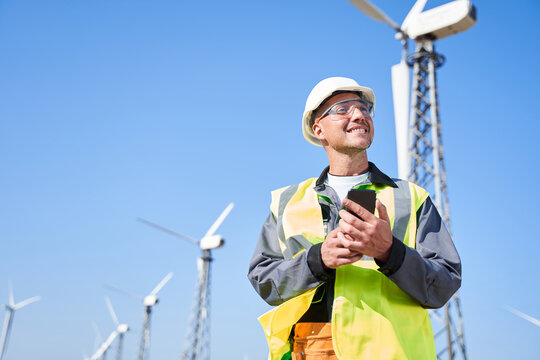 Alternative power concept with worker on windmill background