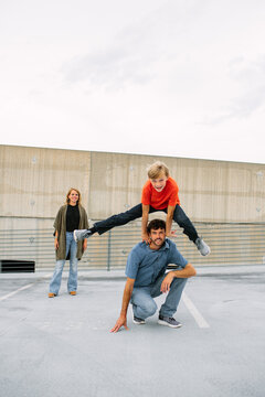 Preteen Son Playing Leap Frog Over Dad's Head