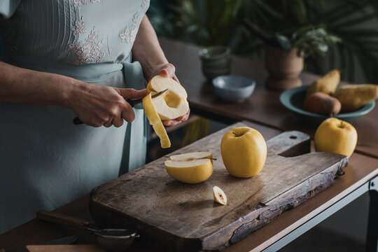 Close Up Woman's Hands Peeling Apples On Wooden Cutting Board