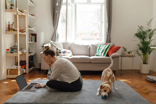 Woman Using Laptop On The Floor Of Her Home