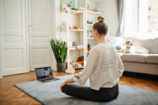 Girl In A Lotus Position Following An Online Yoga Class