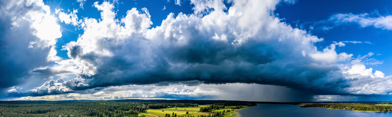Aerial Panorama of Scandinavian pine tree forest landscape, Sunny and Rainy areas around lake, blue sky, white and dark clouds, green yellow fields. View on typical landscape of Northern Sweden