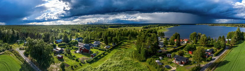 Aerial Panorama of Scandinavian pine tree forest landscape, summer village with Sunny and rainy areas, clear blue sky, white clouds, green yellow fields. View on typical landscape of Northern Sweden