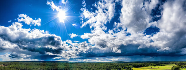 Aerial Panorama of Scandinavian pine tree forest landscape with shiny Sun, brighta sunrays, clear blue sky, white clouds, green yellow fields. Wide view on typical landscape of Northern Sweden