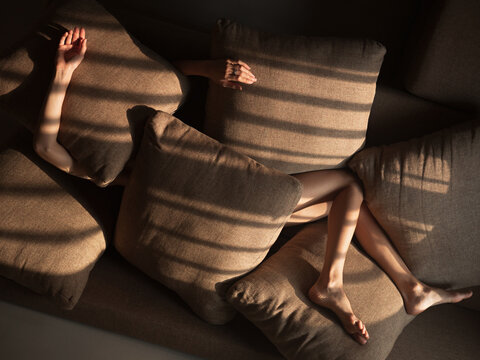 Woman on sofa covered by pillows