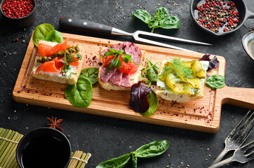 Set of sandwiches with vegetables and salmon on a wooden board. Top view. Rustic style.