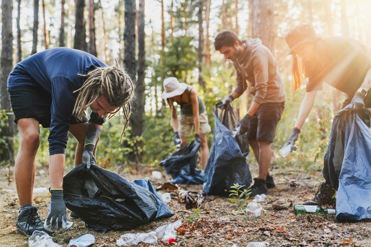 Young men and women picking up litter in forest