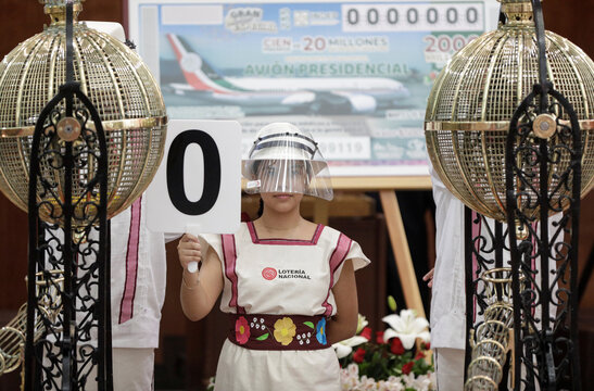 A girl holds a sign of number 0 during a lottery raffle for the value of the last president's luxury plane at the National Lottery building in Mexico City