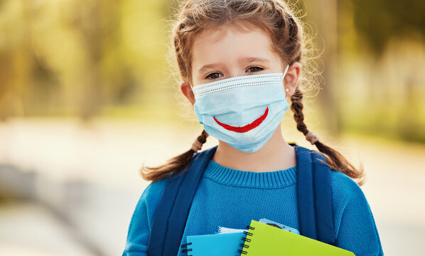 Little school girl in protective mask  .