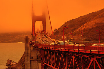 Cars crossing Golden Gate Bridge from Lime point. Smoky orange sky the bridge of San Francisco city for California fires in September 2020 in America. Wildfires composition.