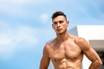 Workout concept portrait of fit shirtless male Caucasian athlete on outdoor rooftop in the sun