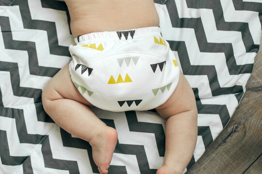 Baby boy in Eco cloth diaper on children's rug. Zero waste, eco-friendly concept. Top view