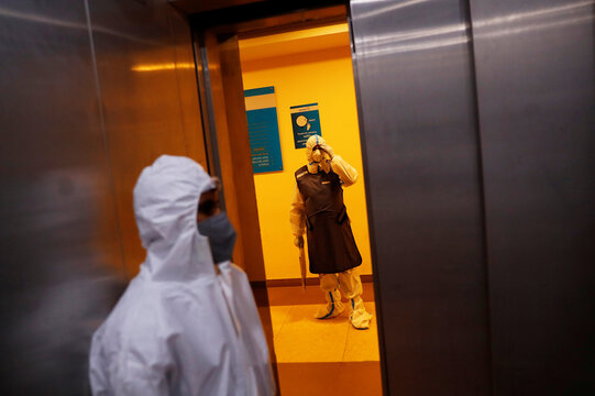 A medical worker holds a X-ray of a patient suffering from the coronavirus disease (COVID-19), waits outside a lift at a hospital in Noida
