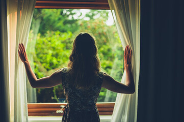 Young woman waking up and opening curtains