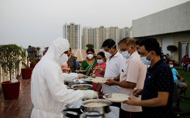 Hospital staff serve food to the patients suffering from the coronavirus disease (COVID-19) during an evening buffet at a hospital in Noida