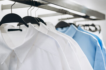 White and blue shirts on hangers in fashion store. Selective focus