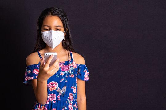 Niña latina con protección mascarilla y celular