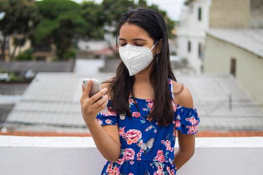 Niña latina con protección mascarilla con celular desde su balcón