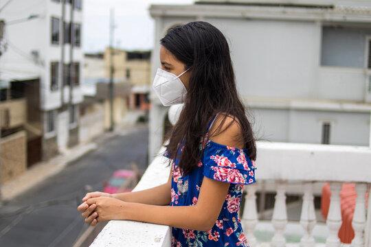 Niña latina con protección mascarilla pensando desde su balcón