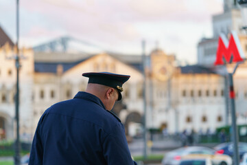 Fototapeta Policeman at the Moscow city street. He wear blue uniform. Old architecture. Red letter M - the sign on entrance into subway. Back / rear view. obraz