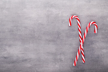 Christmas candy canes, stick and decor on color background. Christmas candy cane heart on an red background.