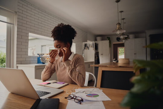 Young female entrepreneur sitting alone blowing nose while using laptop during work from home