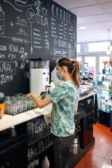 Young waitress with mask cleaning glasses in a coffee shop