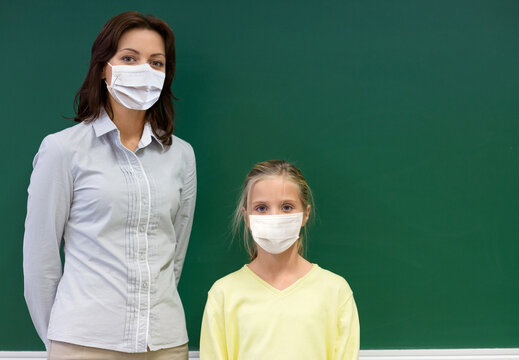 education, school and pandemic concept - little student girl with teacher wearing face protective medical mask for protection from virus disease at green chalkboard in classroom