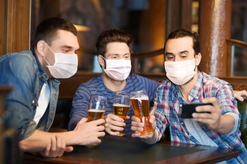 male friendship, leisure and pandemic concept - men or friends in face protective medical masks for protection from virus drinking beer and taking selfie with smartphone at bar or pub