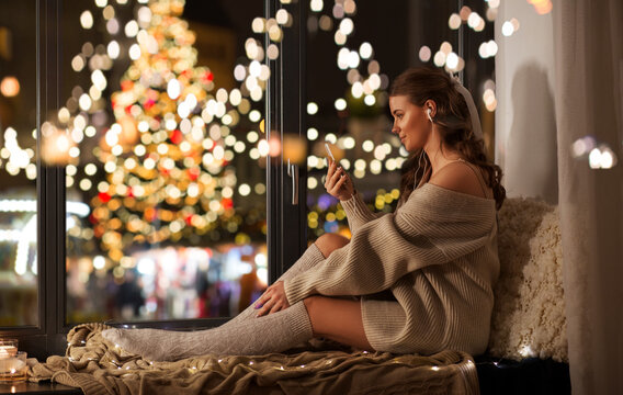 christmas, holiday and people concept - young woman in pullover with smartphone and earphones listening to music sitting on windowsill at home over festive lights on background