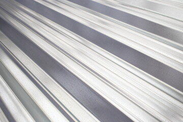 Fototapeta Texture of galvanized shiny metal sheet iron close-up. Shine and light reflection of zinc protective coating in daylight cloudy weather. High robust profile