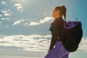 sporting woman single tourist with backpack and rug stands on sky background