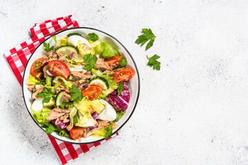 Tuna salad with green leaves, eggs and vegetables.