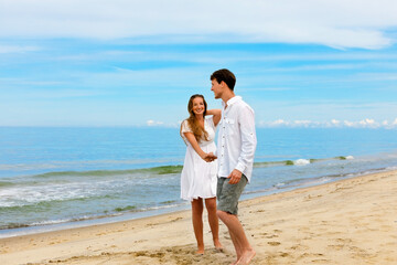 Cute couple of young people in love standing on the sea beach