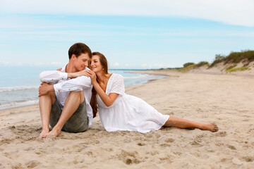 Pleasant couple of young lovers relax on the beach