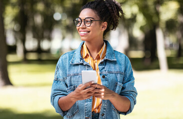 African Student Girl Using Cellphone Walking On Weekend In Park