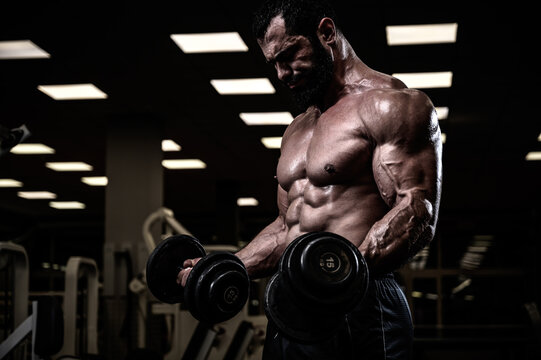 strong young bearded male lifting heavy weight dumbbells training his biceps muscles in dark gym during hard workout