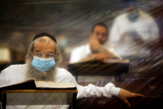 Israeli Jewish worshippers study in a seminar which is fitted with plastic sheets to protect them from the spread of the coronavirus disease (COVID-19) in Ashdod, Israel