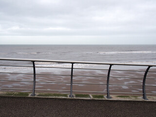 metal railings on the seafront in blackpool with waves breaking on the beach under a cloudy sky