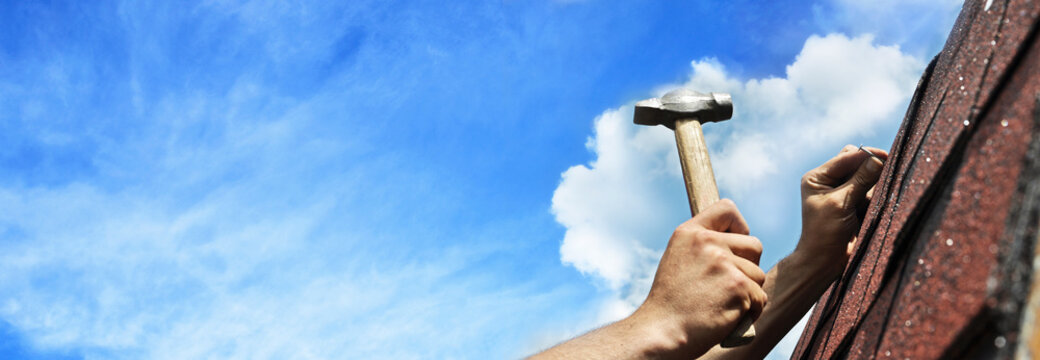 hand with hammer on background of blue sky banner