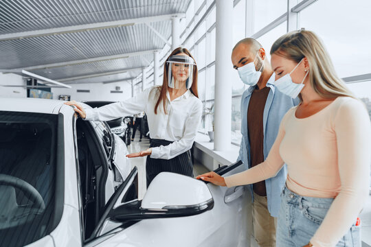 Woman car dealer consulting buyers wearing medical face shield