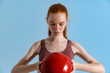 Photo of athletic redhead sportswoman working out with medicine ball