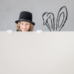 Child magician hiding behind banner blank