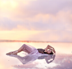 A young girl in an airy dress lies in the water of a pink lake. Artistic gentle magical photo.