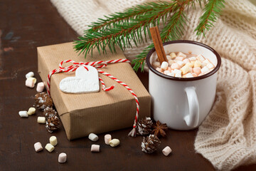 Cup with homemade Christmas hot Chocolate drink, Marshmallows and Holiday Gift on dark background.