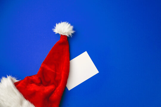 Blank paper sheet and Snata Claus hat on blue background