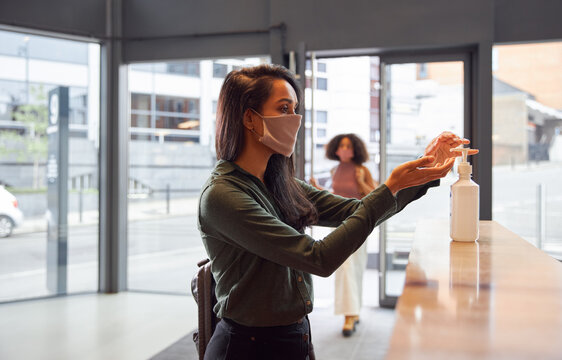 Mixed Race Businesswoman In Face Mask Uses Hand Sanitiser In Office Reception During Health Pandemic